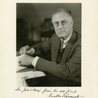 Franklin Delano Roosevelt sitting at his desk signing papers